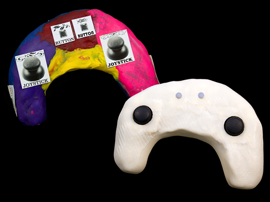 Two game controllers, one made from clay and stickers and one 3D printed from the scanned clay model.
